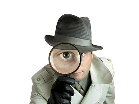 Man looking through magnifying glass